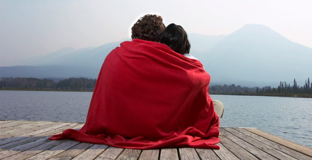 Angela and Ryan under blanket on a pier.